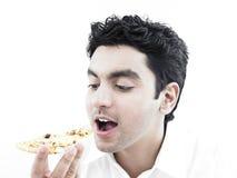 Mangiatore di uomini asiatico una fetta della pizza fotografie stock