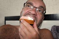 Mangiatore di uomini un panino della salsiccia per la cena immagini stock libere da diritti
