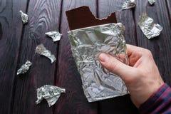Mangiatore di uomini una barra di cioccolato immagini stock libere da diritti