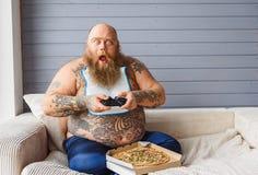 Mangiatore pesante maschio colpito che gioca console Fotografia Stock