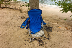 A mangled beach chair in the tropics. A broken chair leaning against a tree at lower bay, bequia Royalty Free Stock Photos