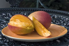 Ripe mangos. Two ripe mangos on a plate placed on a table in a garden Stock Photo
