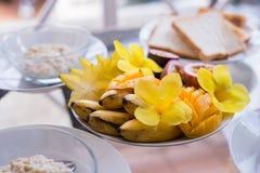 Mango, banana, passion fruit bowl topped with fresh fruit and flowers.  Stock Image