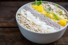 Mango, Banana, Pineapple and Oatmeal Smoothie in the Bowl. With Ingredients on top, on the dark wooden background Stock Images