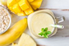 Mango, Banana, Pineapple and Oatmeal Smoothie in the Jar. With Ingredients nearby on the Light Background. Top View Stock Image