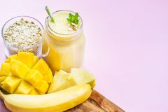 Mango, Banana, Pineapple and Oatmeal Smoothie in the Jar. With Ingredients nearby on the Light Pink Background Royalty Free Stock Photo
