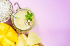 Mango, Banana, Pineapple and Oatmeal Smoothie in the Jar. With Ingredients nearby on the Light Pink Background, Top View Royalty Free Stock Photos