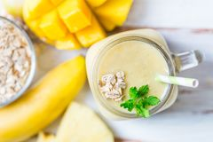Mango, Banana, Pineapple and Oatmeal Smoothie in the Jar. With Ingredients nearby on the Light Background. Top View Stock Photography
