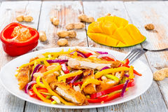 Mango, bread crumbed chicken breast,  peanuts, bell pepper salad Stock Image