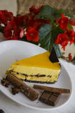 Mango cake slice with coffee beans and red flowers on background Stock Image