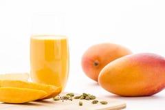 Mango-, cardamon- och mangoyoghurtdrink på vit Arkivbilder