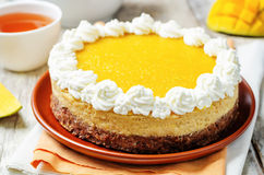 Mango cheese cake decorated with whipped cream and mango puree Royalty Free Stock Image