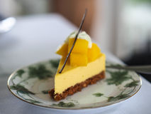 Mango cheesepie topped with fresh mango serves on vintage plate. Yellow mango cheesepie , decorated with fresh cube mangos and dry vanilla stick serves on Stock Photo