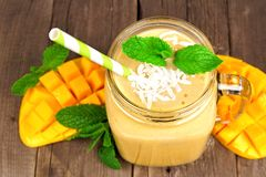 Mango coconut smoothie in a jar, close up over wood. Mango coconut smoothie in a mason jar glass, close up over a rustic wood background Stock Photos
