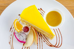 Mango crepe cake serve with mango sauce and fresh fruit. On wooden table Royalty Free Stock Photo
