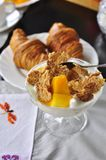 Mango croissant and cornflakes delicious breakfast. Delicious and healthy breakfast with a bowl of fresh mango, cornflakes and yoghourt with croissant and coffee Royalty Free Stock Image