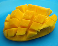 Mango in cubes on blue. Mango sliced into cubes, on blue Royalty Free Stock Image