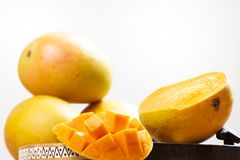 Mango cubes / slices close up / mangos in background. Mango cubes / slices close up / Macro with mangos in background Stock Images