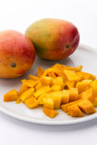 Mango Cubes And Two Whole Mangos On A White Plate Royalty Free Stock Photography