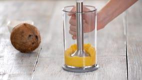 Mango de las rutinas de la mujer con una licuadora Fabricación del puré del mango almacen de metraje de vídeo