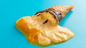 Mango del tiro dello studio mini o cono gelato arancio di sapore che si fonde sul blu stock footage