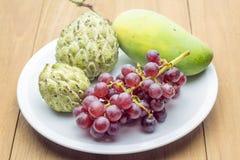 Mango della mela cannella ed uva rossa in piatto bianco Immagini Stock