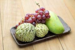 Mango della mela cannella ed uva rossa in piatto di legno Fotografie Stock Libere da Diritti