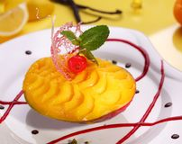 Mango dessert decorated with mint leaf and caramel decoration. stock image