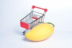 Mango en klein boodschappenwagentje op een witte achtergrond Stock Foto