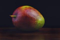 Mango en la tabla de madera, fondo oscuro Imagen de archivo