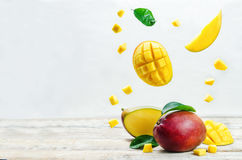 Mango with flying slices. On a white wood background. tinting. selective focus Royalty Free Stock Photos