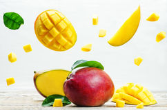 Mango with flying slices. On a white wood background. tinting. selective focus Stock Images