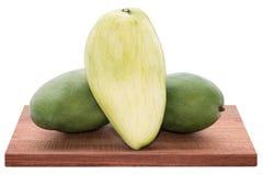 Mango fresco - mangos verdes cortados en de madera con blanco aislado Imagenes de archivo