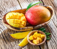 Mango fruit and mango cubes on the wood. royalty free stock images
