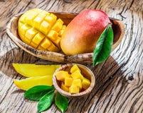 Mango fruit and mango cubes on the wood. Stock Image