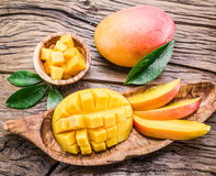 Mango fruit and mango cubes on a wooden table. royalty free stock photography
