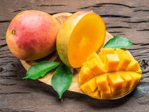 Mango fruits and mango slices on the old wooden table. stock images