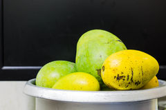 Mango fruits. Raw and ripe manga fruits on rice cooker Royalty Free Stock Photos