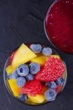 Mango, grapefruit and blueberry smoothie. Fresh fruit salad. Slices of fruits Royalty Free Stock Image