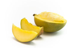 Mango half and sections. Half mango and sections lying on whtie background royalty free stock photos