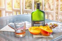 Mango i figi z szkłem brandy na stole na balkonie na słonecznym dniu i butelką Obraz Royalty Free
