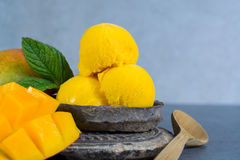 Mango ice cream sorbet with mint leaves and mango fruit in black. Stone bowl Stock Photo
