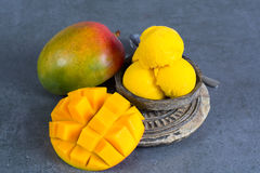 Mango ice cream sorbet with mint leaves and mango fruit in black. Stone bowl Royalty Free Stock Photos