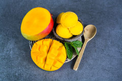 Mango ice cream sorbet with mint leaves and mango fruit in black. Stone bowl Royalty Free Stock Photo