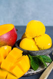 Mango ice cream sorbet with mint leaves and mango fruit in black. Stone bowl Stock Photos