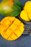 Mango ice cream sorbet with mint leaves and mango fruit in black. Stone bowl Stock Image