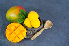Mango ice cream sorbet with mint leaves and mango fruit in black. Stone bowl Stock Images