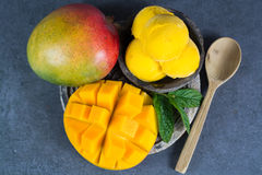 Mango ice cream sorbet with mint leaves and mango fruit in black. Stone bowl Stock Photography