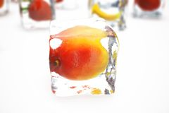 Mango in ice cube isolated on white with depth of field effects. Ice cubes with fresh berries. Berries fruits frozen in. Ice cubes. 3D rendering Royalty Free Stock Image
