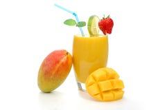 Mango juice. Whole mango resting on a glass with juice Stock Photo